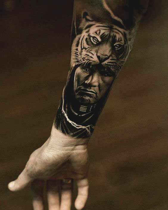 Tiger with men face tattoo on inner forearm
