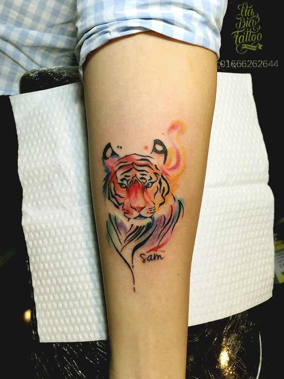 Small watercolor tiger face tattoo on inner arm